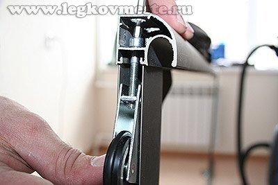 Закрепляем нижние опорные колесики двери шкафа купе