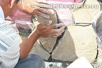 Укладываем на цоколь здания очередной камень