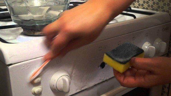 хозяйка чистит плиту зубной щёткой