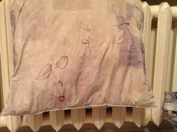 Постиранная подушка сохнет на радиаторе