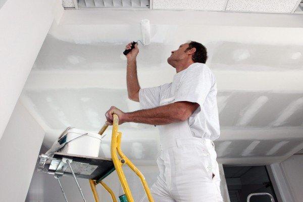мужчина грунтует гипсокартонный потолок перед покраской