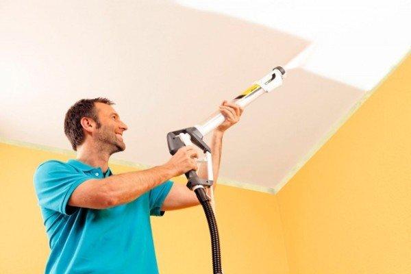 Мужчина красит потолок краскопультом