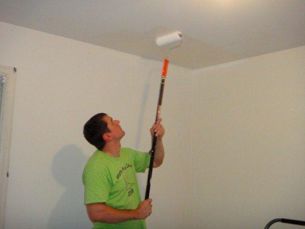 Мужчина красит потолок валиком