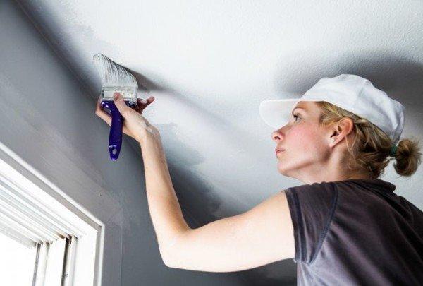 Женщина красит потолок