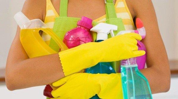 девушка держит моющие средства