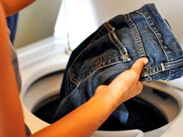 женщина достаёт джинсы из стиральной машины