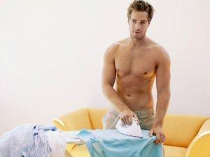 Мужчина гладит рубашки
