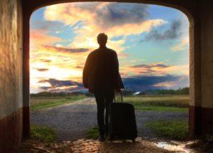 Мужчина с чемоданом на колёсах