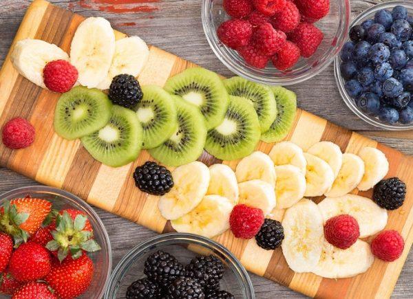 Нарезанные банан и киви с ягодами на разделочной доске