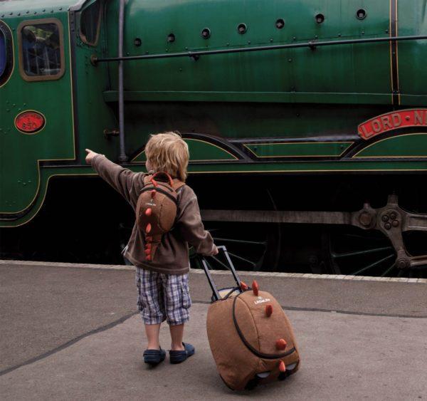 Ребёнок перед поездом с чемоданом-драконом
