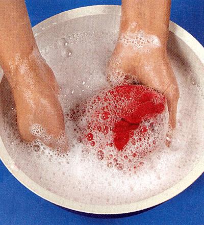 Руки стирают подкладку в тазике