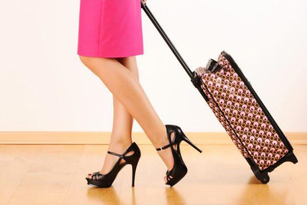 Женщина в розовом платье и на каблуках везёт цветной чемодан