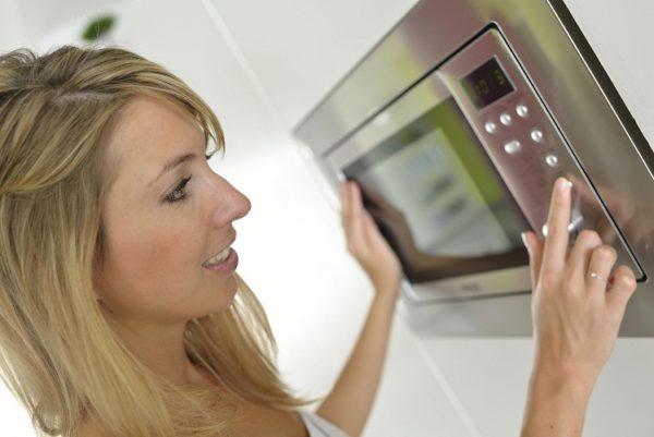 Женщина включает микроволновку