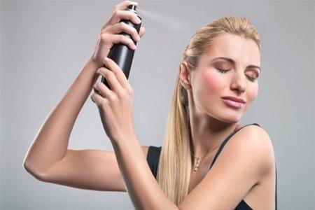 Блондинка брызгает волосы лаком