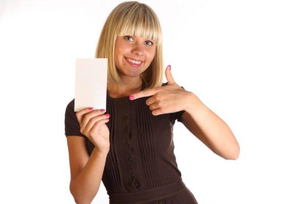 Блондинка держит белый лист бумаги в руке, другой рукой указывает на него