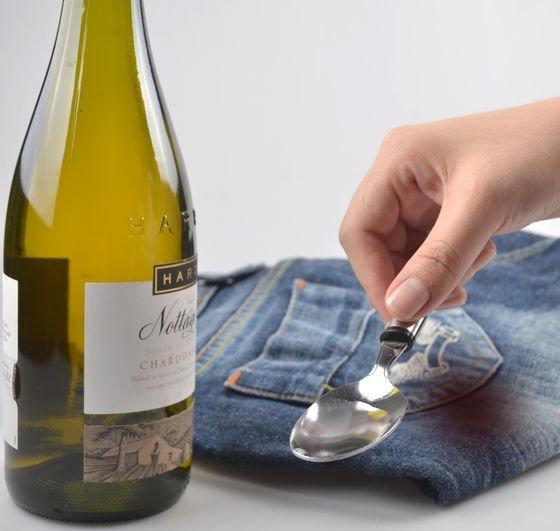 Бутылка с белым вином, джинсы и ложка с жидкостью
