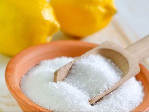 Лимонная кислота в мисочке, на заднем фоне 2 лимона