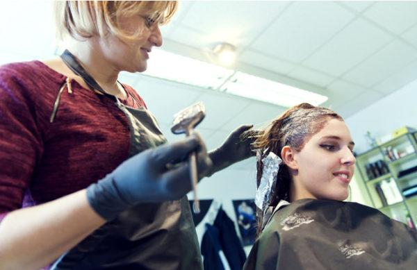 Мастер наносит краску для волос девушке в кресле