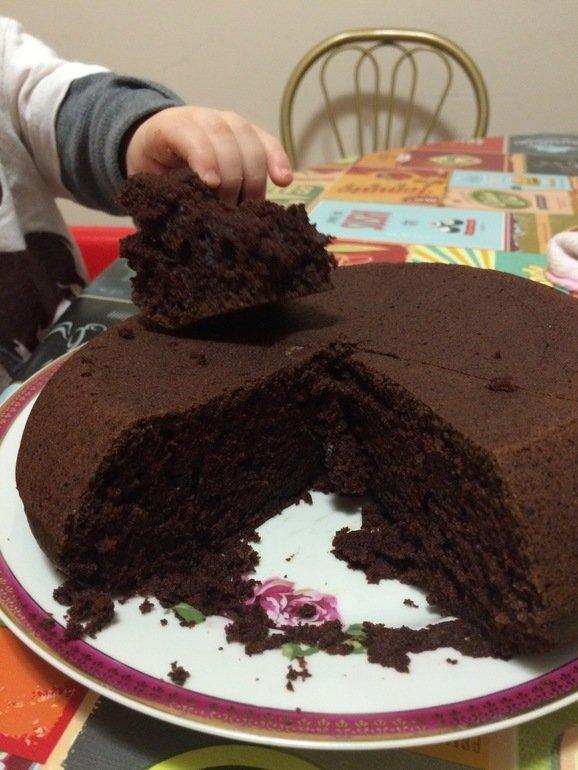 Ребёнок берёт кусок шоколадного пирога