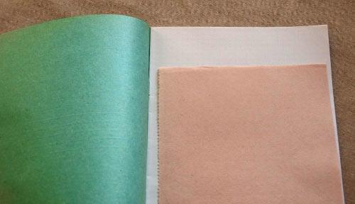 Розовая промокашка на открытой тетради с зелёной обложкой