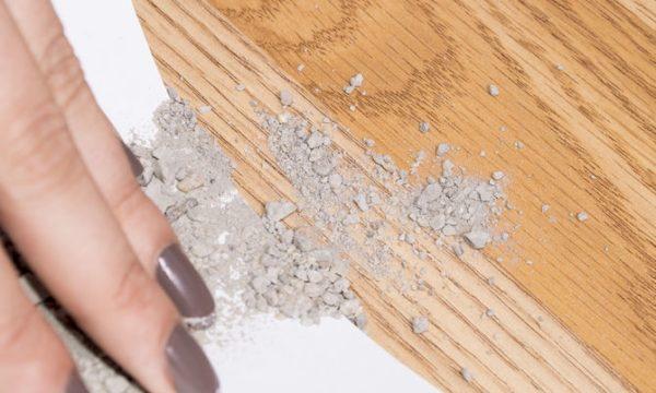 Рука распределяет частички пемзы по поверхности паркета