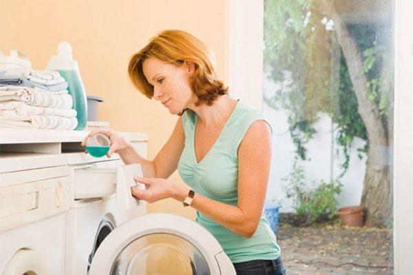 Женщина загружает машинку бельём, наливает средство для стирки