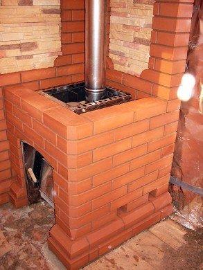 Металлическая печь с кожухом из красного кирпича