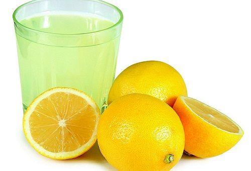Стакан с разведённой лимонной кислотой, лимоны