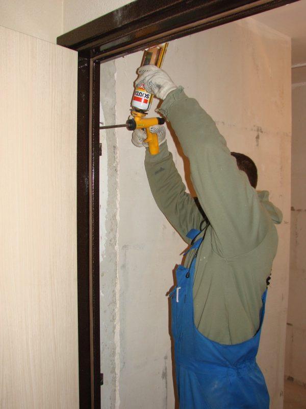 Строитель задувает пеной косяк металлической двери