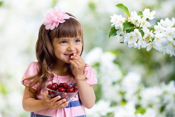 Девочка кушает вишню