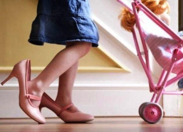 Девочка в больших розовых туфлях везёт игрушечную коляску