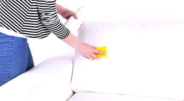 Рука жёлтой тряпкой вытирает белый диван