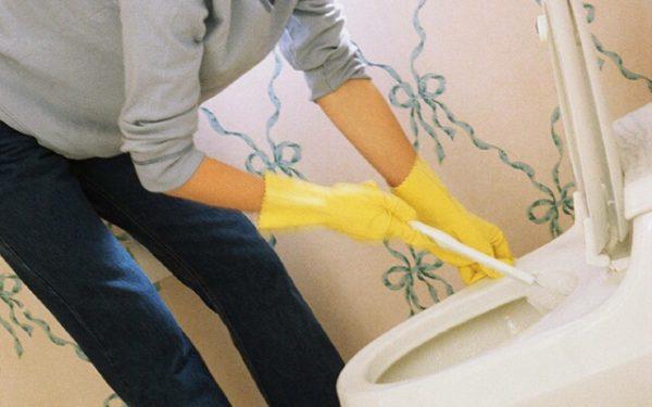 Руки в жёлтых перчатках чистят унитаз