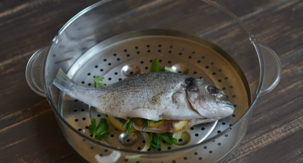 Размороженная рыба дорадо на решётке пароварки