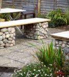 Деревяная скамейка на опорах из камней