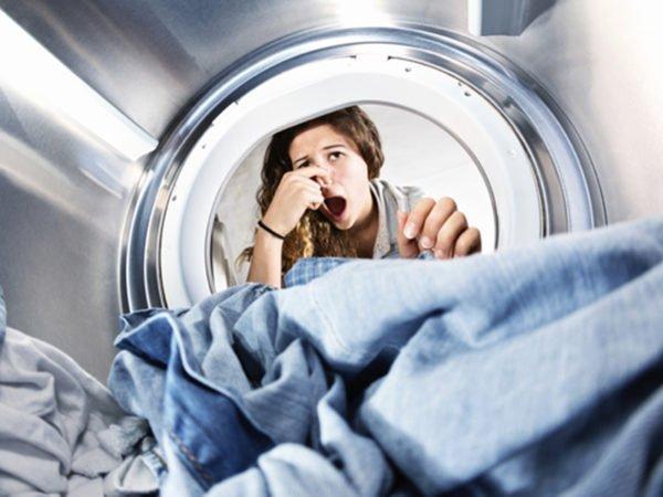 Девушка, затыкающая нос, заглядывая в стиральную машину