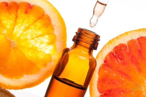 Половинки апельсина и пузырёк с эфирным маслом
