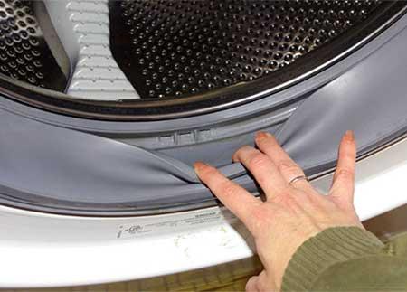 Рука, оттягивающая резиновую манжету стиральной машины