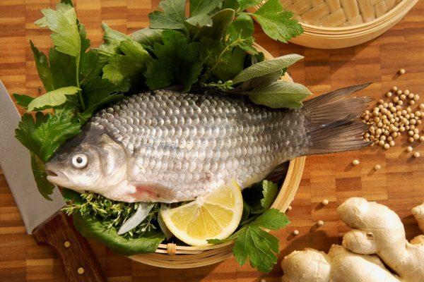 Рыбы в деревянной миске с лимоном и листьями