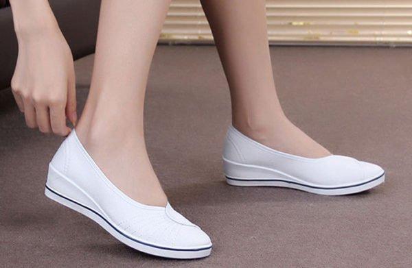 Белые балетки на женских ножках