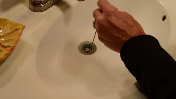 Рука прочищает раковину тросиком из проволоки