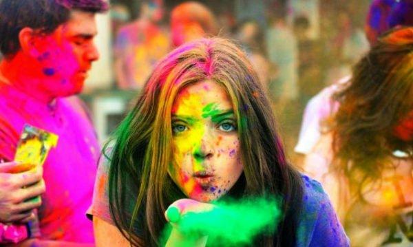 Девушка, сдувающая с ладони краску холи