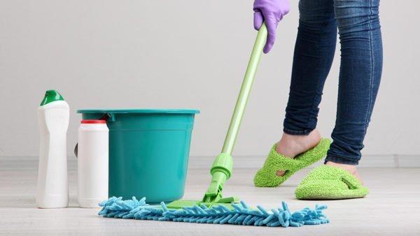 Girl in green slippers mops the floor