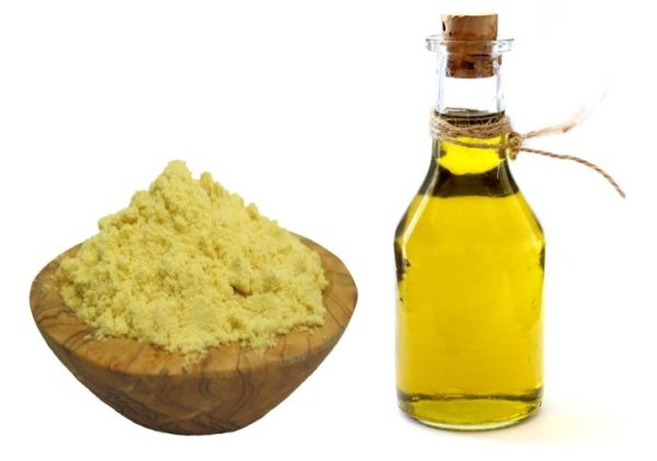 Mustard powder in a wooden bowl and a bottle of vegetable oil