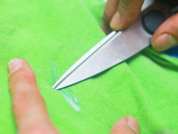 Ножницами убирают след от ПВА с зелёной ткани