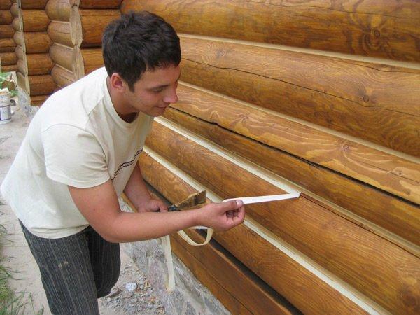 Процесс заделки швов между брёвнами деревянной постройки