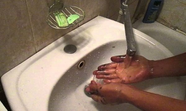 The hands in the potassium permanganate are washed in the sink