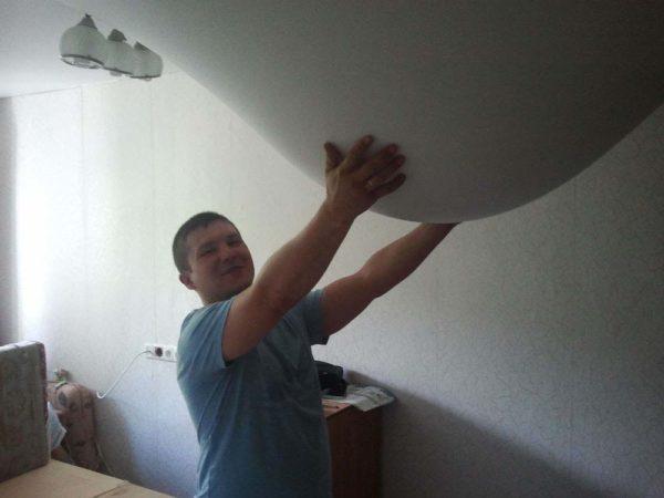 Мужчина придерживает обвисший натяжной потолок