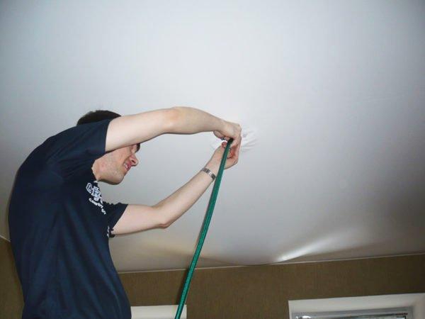 Вставляют резиновый шланг в отверстие в натяжном потолке