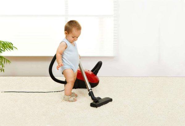 Ребёнок пылесосит ковёр